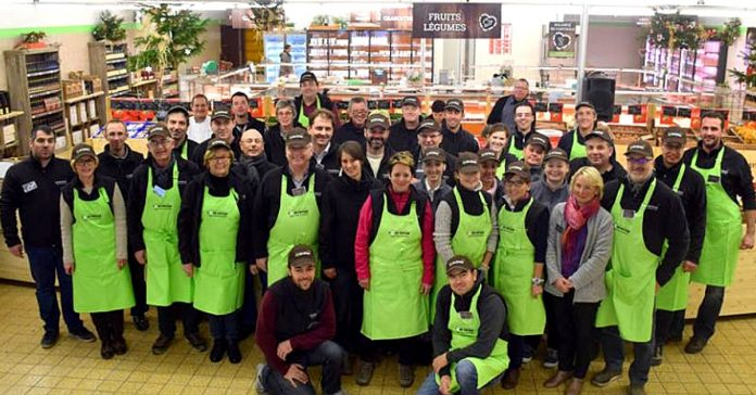 About 20 armers with a green apron standing, posing as a group for the photo inside the supermarket