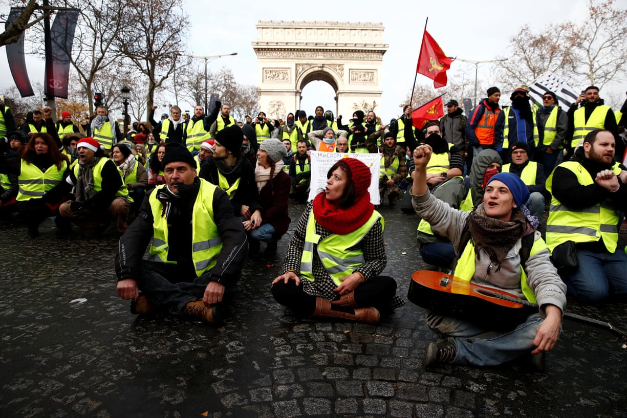 demonstrators wearing yellow vests, some seating, some standing, protesting in from of the 'Arc de Triomphe' in Paris