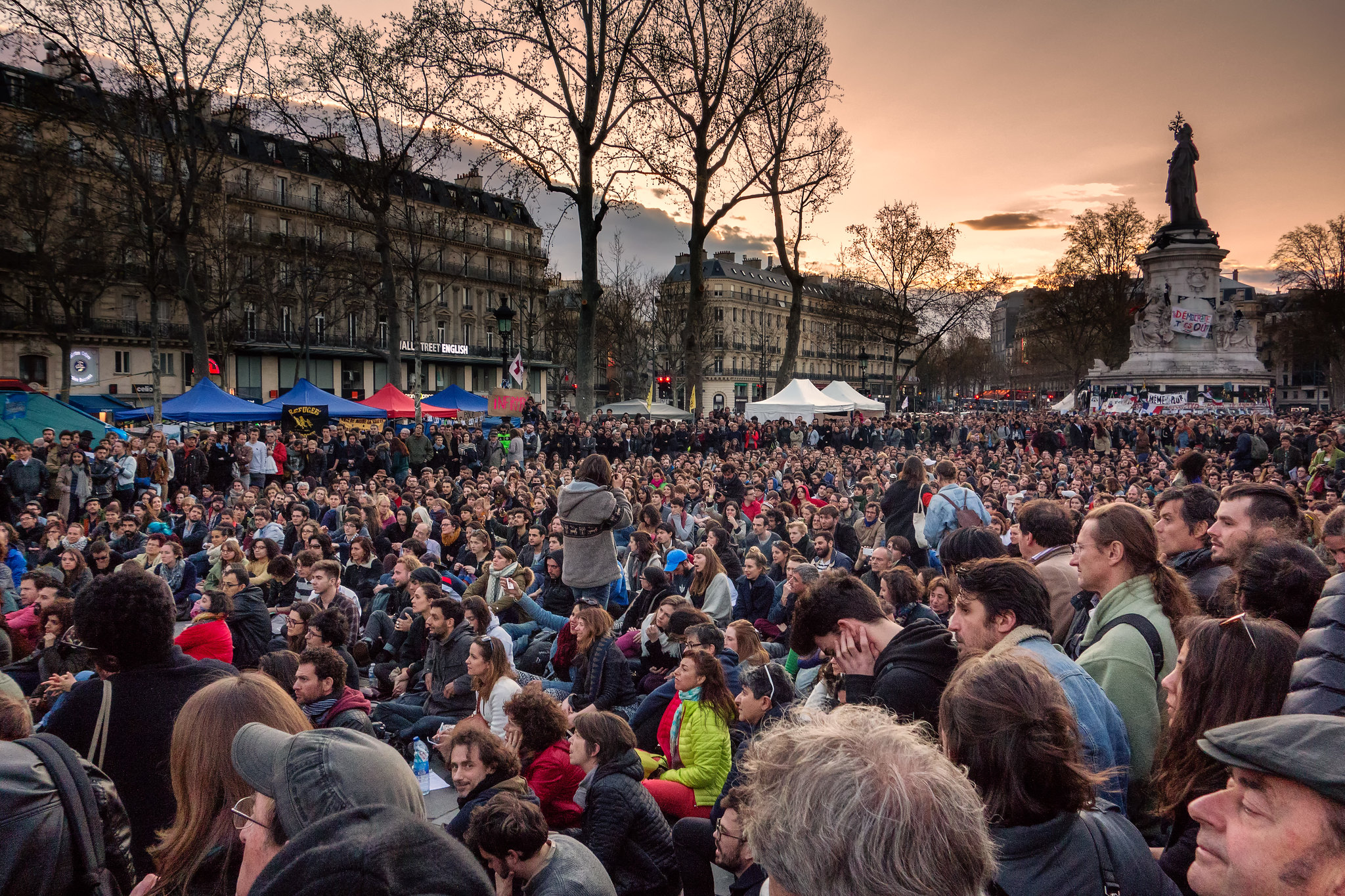 Crowd of people gathered on Place de la République in Paris listening to someone speaking