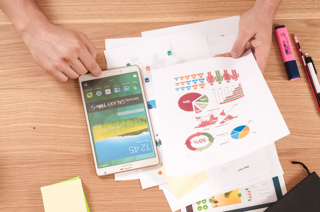photo of a desk with someone working with paper showing graph, pie charts and a phone