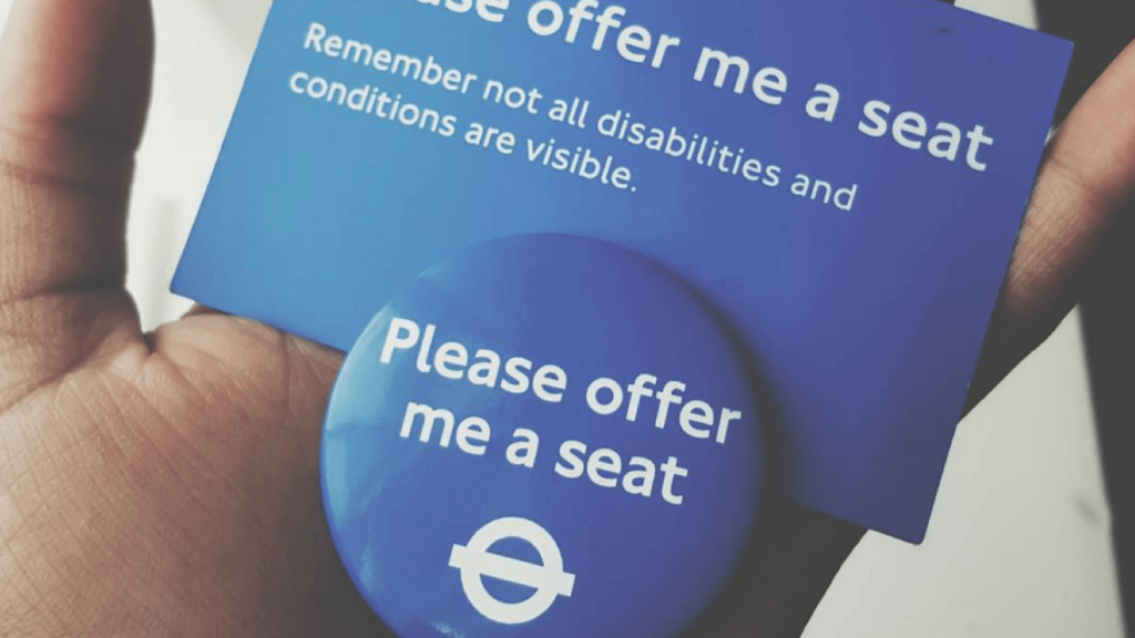 "A badge and a card from Transport London stating: ""please offer me a seat"""