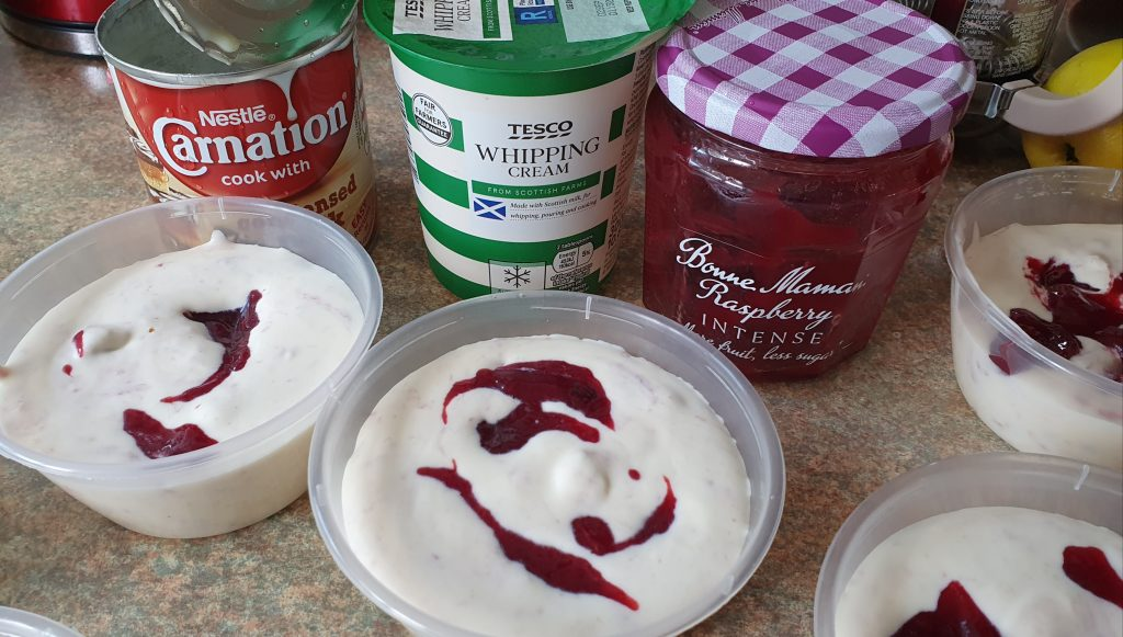 little pots of ice cream with trace of jam at the top, behind, there is a pot of whipping cream, a pot of jam and a tin of condensed milk