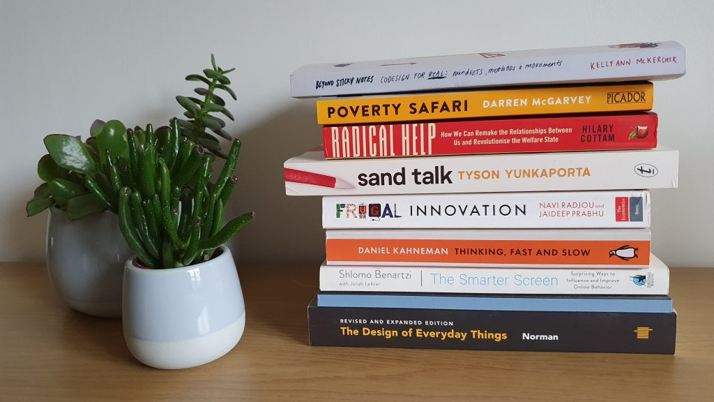 pile of books next to two plants. At the top of the pile, it's Beyond Sticky notes by Kelly Ann Mc Kercher, just under is Poverty safari by Darren McGarvey, then Radical help by Hilary Cottam, Sand Talk by Tyson Yunkaporta, Frugal innovation , then think fast and slow, then the smarter screen, and finally the Design of everyday things by Norman